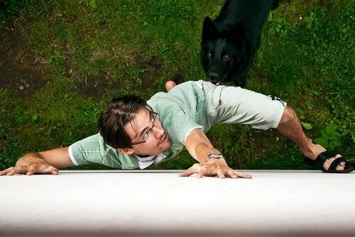 mand, der forsøger at kravle væk fra en hund