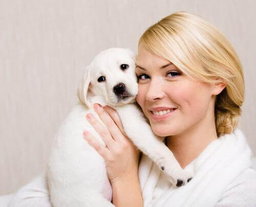 Kvinde krammer hundehvalp og viser, at hunde ligner deres ejere i mange tilfælde