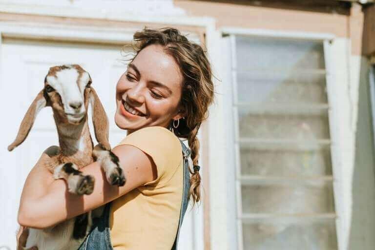 En kvinde illustrerer pasning af geder