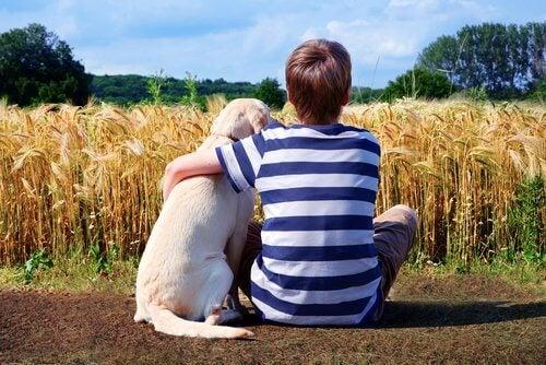 dreng der har sin arm om en hund