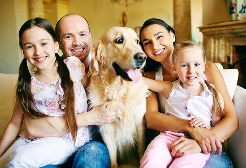 Glad familie med en stor hund