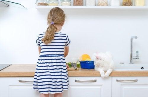 En kat, der sidder på et køkkenbord, mens en pige laver mad