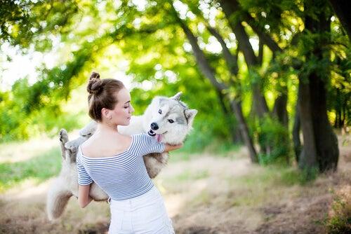 Nainen kantaa koiraa