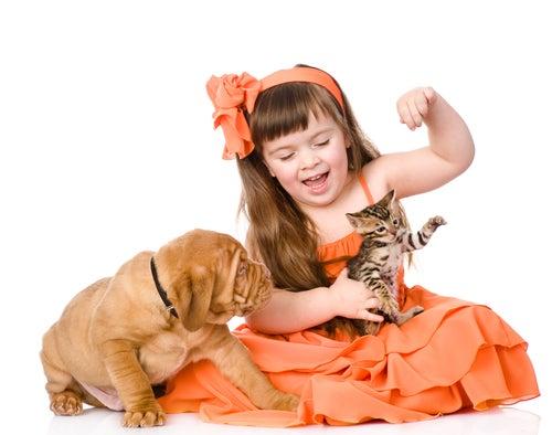 Une petite fille joue avec un chiot et un chaton