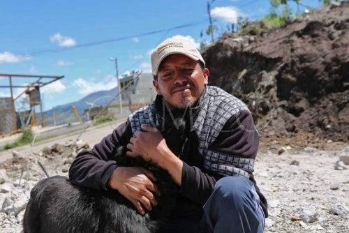 homme qui prend dans ses bras un chien après un tremblement de terre