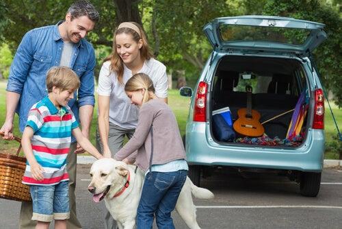 Un famille et leur chien face au coffre ouvert d'une voiture