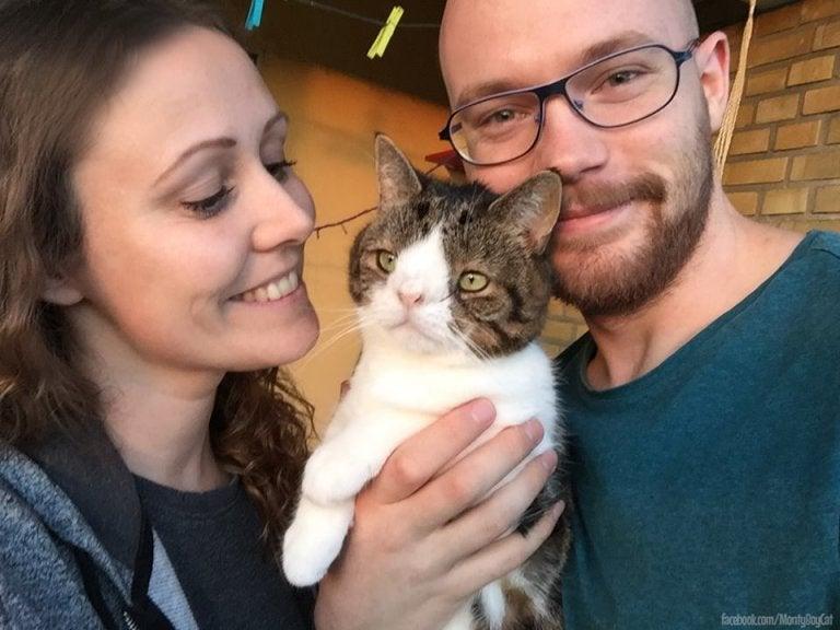 Le chat Monty se tient avec ses maîtres Michael et Mikala