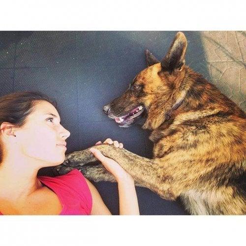 Une femme est allongée au sol avec son chien et ils se regardent
