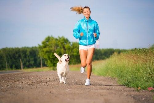 Une femme court à côté de son labrador beige