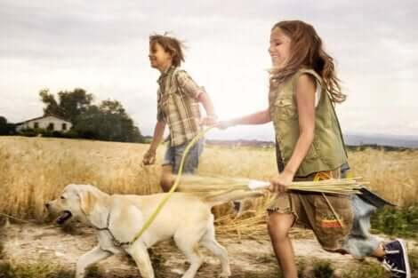 Des enfants qui courent avec leur chien.