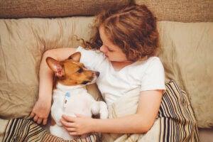 Une petite fille allongée sur son lit avec son chien.