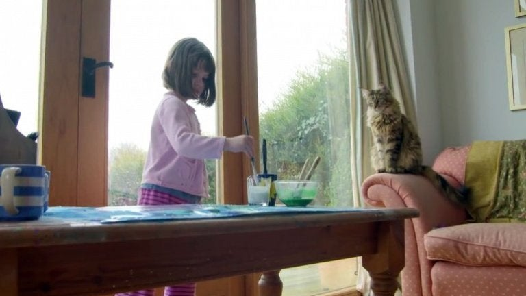 絵を描く少女を見つめる猫
