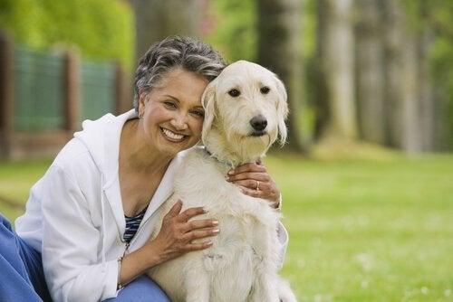 eldre dame som holder rundt hunden sin