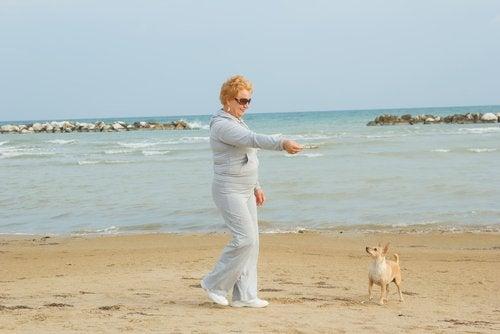 Kvinne trener på stranden med hund.