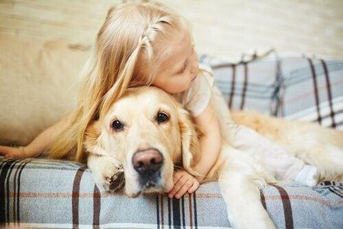 Liten blond jente koser med en stor golden retriever på sofa.