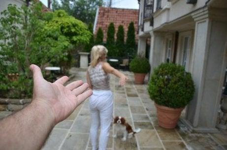 En kvinne, en hund og en tilsynelatende mannlig hånd på en gårdsplass