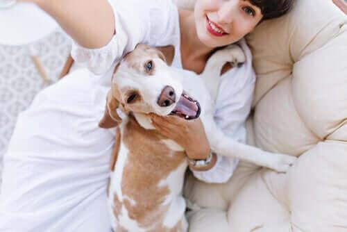En kvinne som klemmer hunden sin