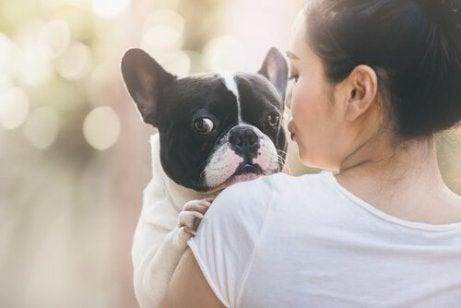 kvinne med hund på armen
