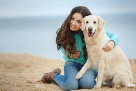En jente og hunden hennes på stranden