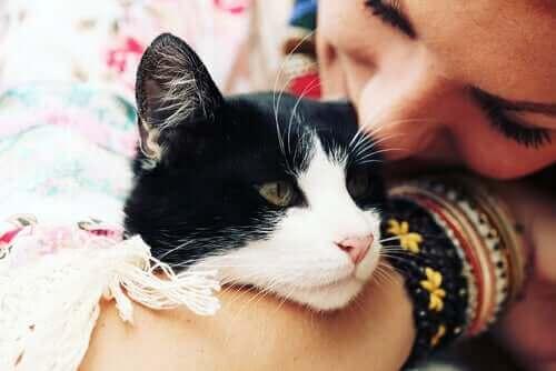 En kvinne som holder og kysser en katt