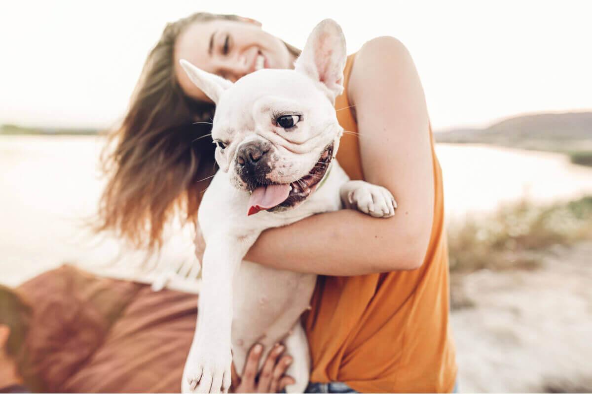 En eier som holder hunden sin på stranden