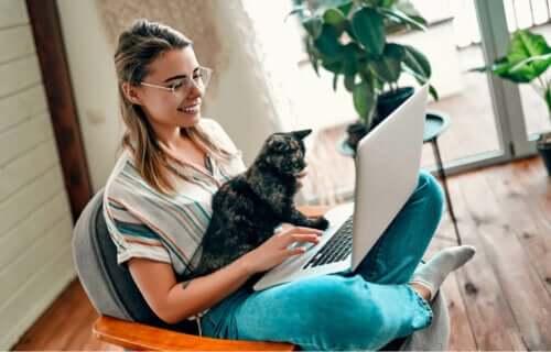 En kvinne som holder en bærbar datamaskin og en lapcat.