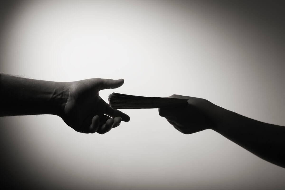 Silhuetten til en person som gir penger til en annen