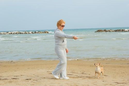 Vrouw speelt met hondje aan het strand