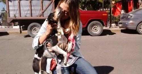 Een eigenaar die haar hond op straat knuffelt