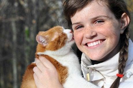 Kat die aan het haar van haar baasje likt