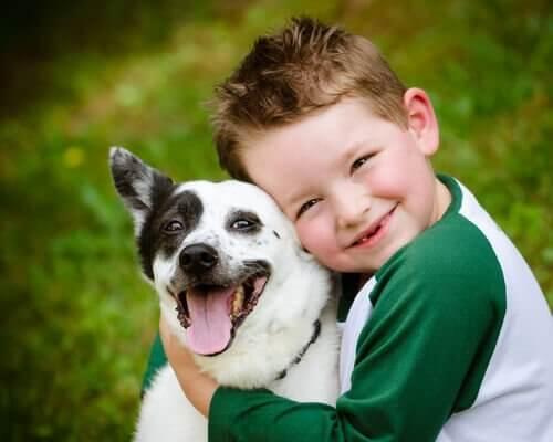 Jongetje dat zijn hond knuffelt