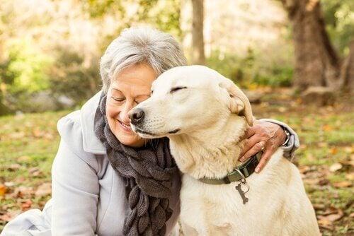 Een vrouw geeft haar hond een knuffel