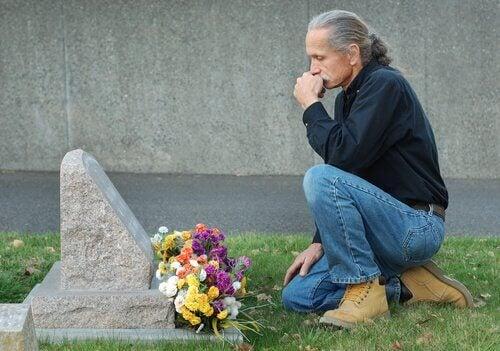 Een man zit bij het graf van zijn huisdier