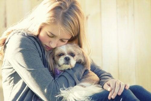 Flicka som kramar hund.