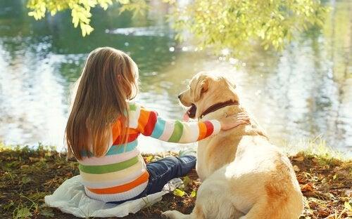 En flicka som sitter med sin hund vid en flod