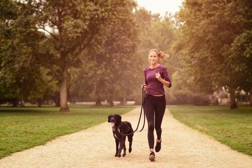 Kvinna som springer med hund.