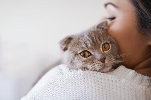 Kvinna som håller katten mot axeln.