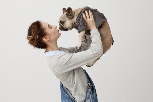 Kvinna som lyfter upp hund.