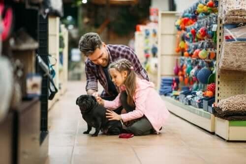 Far, dotter och hund i djuraffären.