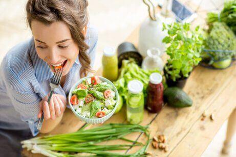 Glad kvinna med sallad äter färska grönsaker för att hon kommer att sluta äta kött.