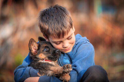 Ett barn kramar sin valp.