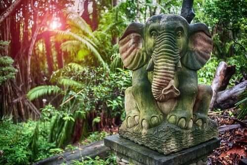 Stenstaty av en elefant i djungel.