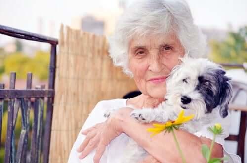 Äldre person med hund i famnen.