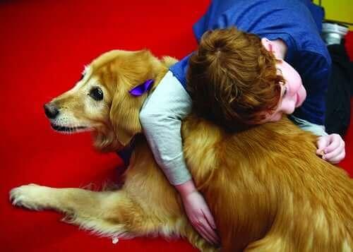 Ett barn i terapi ger en hund en stor kram.