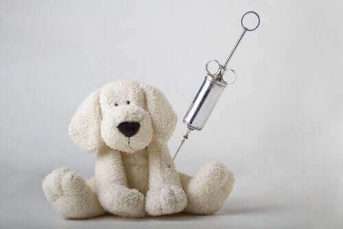 Leksakshund med en spruta i armen.