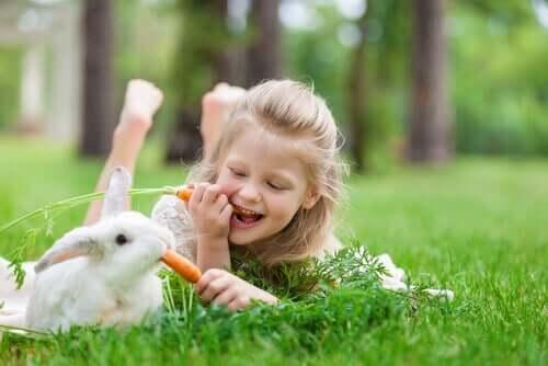 Flicka äter morot med sin kanin.