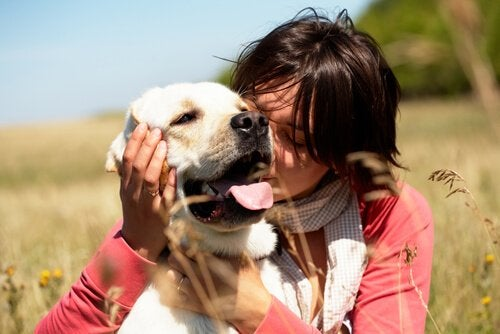 A woman hugging her happy dog.