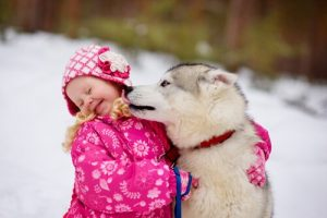 Dog licking a little girl on the face