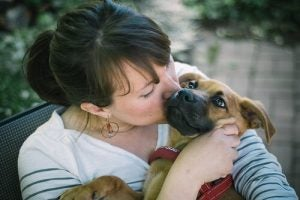 A woman kissing a dog