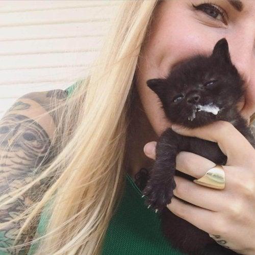 Kitten Lady holding a black kitten